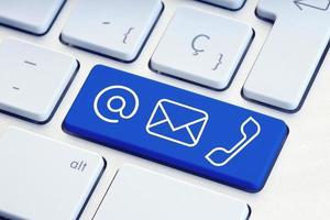 Contáctenos conjunto de signos en la tecla azul del teclado de la computadora foto