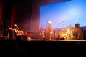 Escenario musical con músicos borrosos ensayando antes del concierto en un auditorio. foto