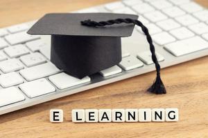 e learning o concepto de estudio en el hogar gorra de graduación en el teclado de la computadora foto