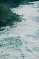 An aerial shot of a massive wild coast in spain with the waves crashing against it photo