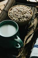 A breakfast of a cup of oat milk with oat seeds over a wooden plank photo