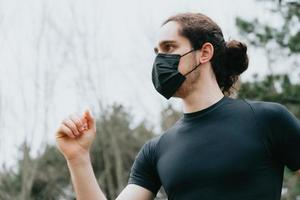 A close up of a young male running in the park while using a face mask photo