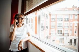Old woman making a call on the mobile phone while looking through the window photo