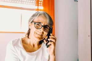 Close up of an old female taking a call on the phone while smiling in his bedroom photo