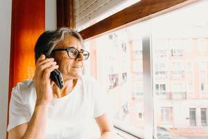 Close up of an old woman making a call on the mobile phone and smiling while looking through the window photo