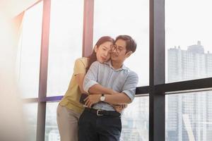 Happy couple cuddling standing  next to big window photo