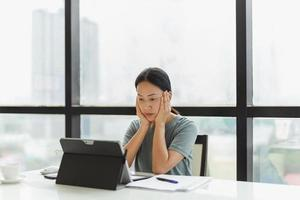 Portrait of business woman working on laptop with hands on her cheek photo