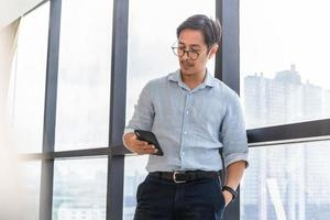 Asian businessman standing next to big window looking at cell phone photo