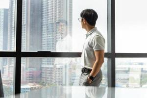 Businessman standing in office building looking through window photo