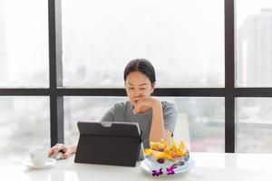 Businesswoman working on laptop with bowl of fresh fruits on table photo