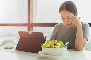 Selected focus on bowl of vegetable salad with woman working on laptop photo