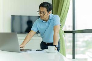 Businessman in glasses leaning over table and work on laptop in office photo