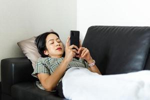 Mujer con teléfono inteligente mientras está acostado en el sofá concepto de cuarentena foto