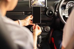 Mujer cargando la batería del teléfono inteligente en el coche foto