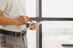 Businessman standing next to the window in his office holding digital tablet photo