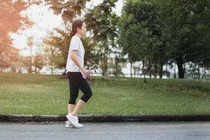 Woman exercise walking in  the park with hand holding bottle water photo
