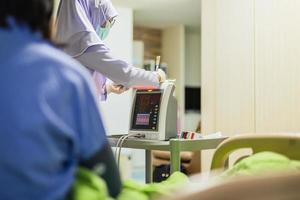 Muslim woman nurse writing on clipboard measuring blood pressure of senior patient photo