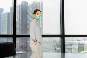 Woman in protective mask standing next to the big window in office photo