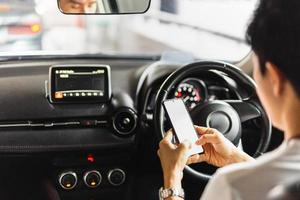 Man using smartphone while driving a car photo
