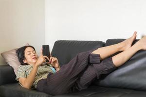 mujer acostada en un sofá con smartphone foto