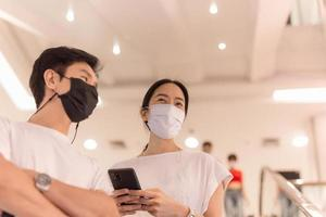 Couple in protective mask standing on escalator in the shopping mall photo