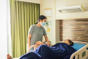 Daughter in medical mask visiting her mother lying in bed at hospital ward photo