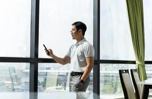 Businessman standing in office building window looking at cell phone photo