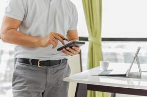 Businessman working on cell phone with laptop on table photo
