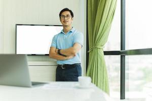 Confident businessman with arms crossed against screen in an office photo