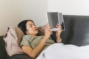 Woman lying on the sofa and reading a book quarantine concept photo