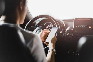 Man using smart phone while driving photo