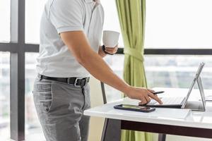 empresario revisando el correo electrónico en la computadora portátil y sosteniendo una taza de café foto