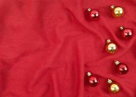 Red and gold Christmas balls on a red textile background photo