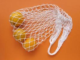 White string cotton eco bag with oranges on orange background Monochrome simple flat lay Ecology zero waste concept Stock photo