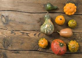 Variety of pumpkins on a wooden background Harvest concept flat lay with copy space photo