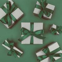 Cajas de regalo envueltas en papel artesanal con cintas verdes y lazos planos monocromáticos festivos foto
