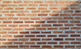 Textura de fondo de pared de ladrillo rojo antiguo con luz a través foto