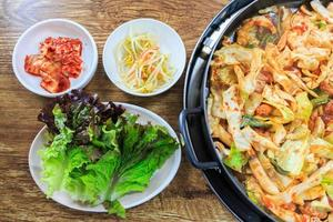 Korean food compose of kimchi  fresh lettuce  bean sprouts and stir fried vegetables with chicken on wood table photo
