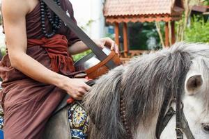 Monje budista con túnica marrón monta a caballo y pide limosna sin ser visto en Tailandia en el templo del caballo de oro de la cueva salvaje en chiangrai, Tailandia foto