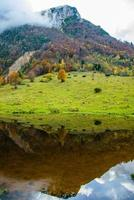 Alpine peaks reflected in autumn photo