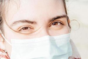 Un super primer plano de una mujer mirando a la cámara mientras usa un concepto de protección de máscara facial foto
