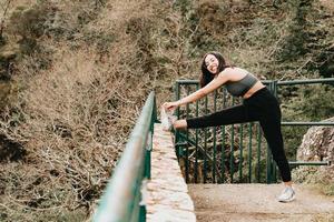 Mujer joven en ropa deportiva estirando su pierna sobre una acera en medio de un bosque otoñal mientras sonríe a la cámara copia espacio concepto de fitness foto