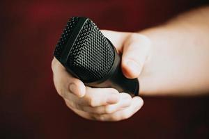 una mano agarrando un micrófono sobre un fondo rojo foto
