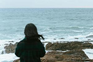 Woman giving the back to the camera in front of a massive ocean with copy space photo