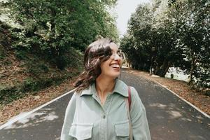 Young Moroccan woman smiling to camera in autumnal and desaturated colors with copy space and modern clothes photo