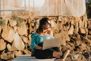 Young woman happy using his laptop on the docks during a super sunset during a super sunny day with copy space work outdoors concept photo