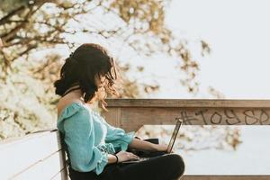 Young woman happy using his laptop on the park during a super sunset during a super sunny day with copy space work outdoors concept photo