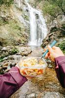 Female hiker eating in front of a waterfall photo