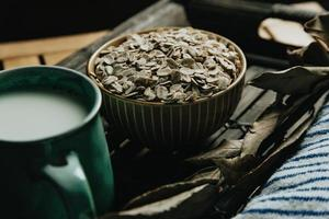 Bowl filled with oat seeds on a wooden table photo