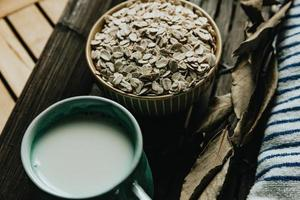 A breakfast of a cup of oat milk with oat seeds photo